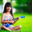 Little asian girl sitting on grass and play ukulele — Stock Photo