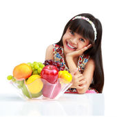 Happy little asian girl sitting on the table with plate of fruit — Stock Photo