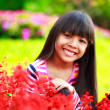 Closeup smiling little asian girl sitting on flower field — Stock Photo