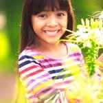 Smiling little asian girl standing on flower field — Stock Photo