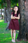 Happy young asian girl standing near a tree in a park — Stock Photo