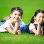 zwei kleine Asiatinnen, die Verlegung auf das grüne Gras — Stockfoto #31348155