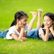 Two little asian girls laying on the green grass — Stock Photo