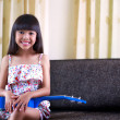 Smiling little asian girl sitting with ukulele — Stock fotografie