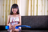 Smiling little asian girl sitting with ukulele — Stock Photo