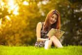Asian woman using digital tablet in park — Stock Photo