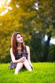 Bellissima giovane donna asiatica, seduto sull'erba verde — Foto Stock