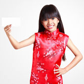 Smiling little asian girl with cheongsam respecting holding empt — Stock Photo