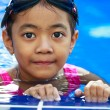 Closeup cute little asian girl resting on the edge of swimming p — Stock Photo