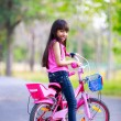 Cute little asian girl on her pink bike — Stock Photo