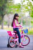 Cute little asian girl on her pink bike — ストック写真