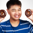 Little asian boy holding a chocolate donuts — Stock Photo