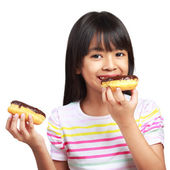 Little asian girl holding and eating chocolate donuts — Stock Photo