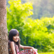 Stock Photo: Smiling little asian girl sitting under a tree