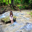Little girl sitting on stone in a forest stream — Stock Photo
