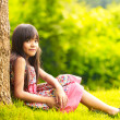 Smiling little asian girl sitting under a tree — Stock Photo