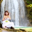Young woman relaxing in water stream near waterfall — Stock Photo