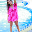 Beautiful young woman standing in a swimming pool — Stock Photo #35019891
