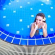 Young woman standing in a swimming pool — Stock Photo