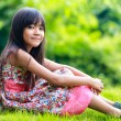 Young asian girl sitting on the green — Stock Photo