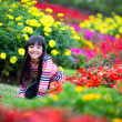 Smiling little asian girl sitting on flower field — Stock Photo