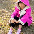 Sad beautiful little girl in pink coat — Stock Photo