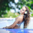 Beautiful young girl relaxing on the swimming pool — Stock Photo