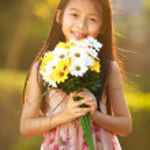 Smiling asian girl hold flowers — Stock Photo