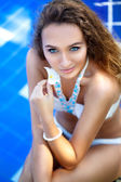 Portrait of a sexy young woman sitting by the swimming pool — Stock Photo