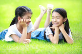 Две азиатские девочки, лежа на зеленой траве — Стоковое фото