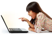 Surprised girl pointing to the computer — Stock Photo