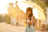 Pretty young asian girl in the rain — Stock Photo