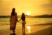 Mother and daughter standing on the beach — Stock Photo