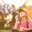 Little asian girl blowing soap bubbles — Stock Photo #46141007