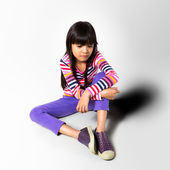 Sad little girl sitting on the floor — Stock Photo
