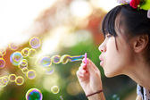 Close up teenager girl blowing soap bubbles — Stock Photo