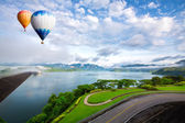 Hot air balloon ffloating over dam — Stok fotoğraf