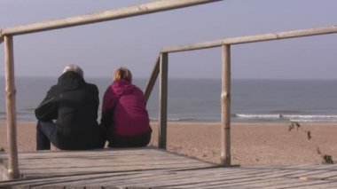 A senior couple relaxing on the seaside — Stock Video