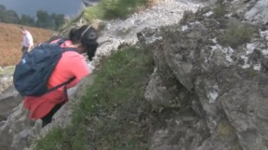 Woman climbs steep rock — Stock Video