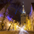 Stock Photo: Illuminated street in Old Town of Tallinn, Estoniat night. Church St. Olaf in background.
