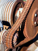 Rusty chain transmission consist of one big and a small cogwheel and large strong chain — Stock Photo
