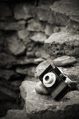 Small SLR film camera on rocks — Stock Photo