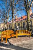 Stora gula eller orange trä bänkar i en park — Stockfoto