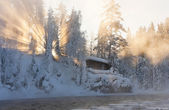 Hut nea water and misty forest in winter — Stock Photo