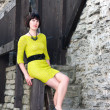 Stock Photo: Womin yellowish dress sit on handrail