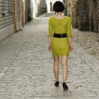 Stock Photo: Womin yellowish dress walks on street