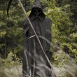 Death standing with scythe on hand — Stock Photo