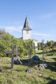 Graveyard crosses and white church — Stock Photo