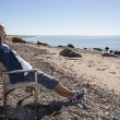 Young man sit and relax on chair at beach — Stock Photo #32057075