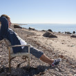 Young man sit and relax on chair at beach — Stock Photo